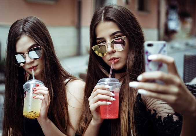 Two girls with sunglasses taking a selfie